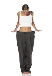 woman holding out waistline of oversized pants